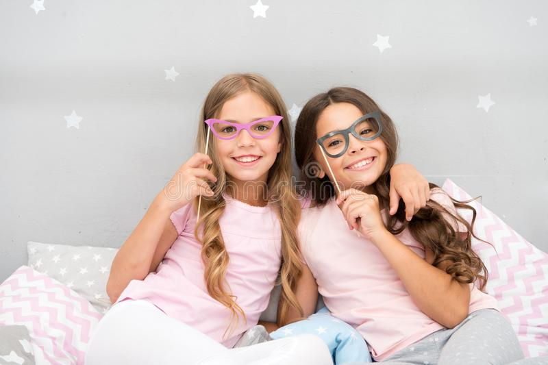Birthday girl. Children posing with grimaces photo booth props. Pajamas party in bedroom. Friends cute and cheerful. Posing with eyeglasses accessories. Girls royalty free stock image