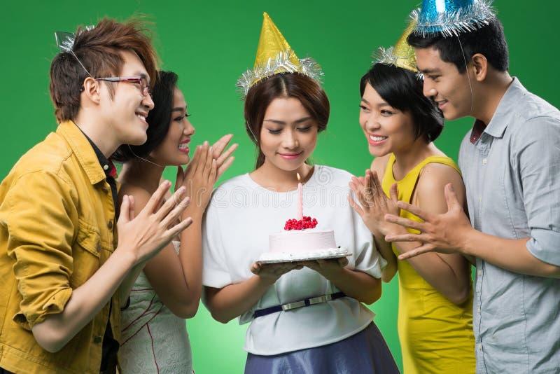 Birthday girl. Happy friends around birthday girl holding a cake royalty free stock photo