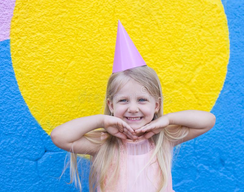 Birthday girl. Happy little girl with birthday cap on head holding hands next to her chin royalty free stock image