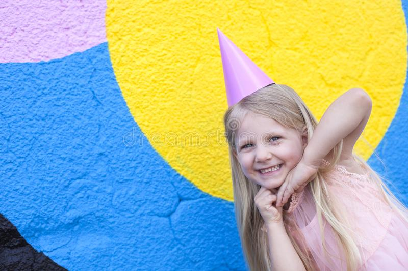 Birthday girl. Happy little girl with birthday cap on head holding hands next to her chin royalty free stock images