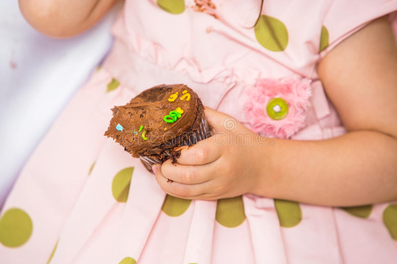 Birthday Girl Holding Cupcake. Midsection of birthday girl holding cupcake at home royalty free stock photo