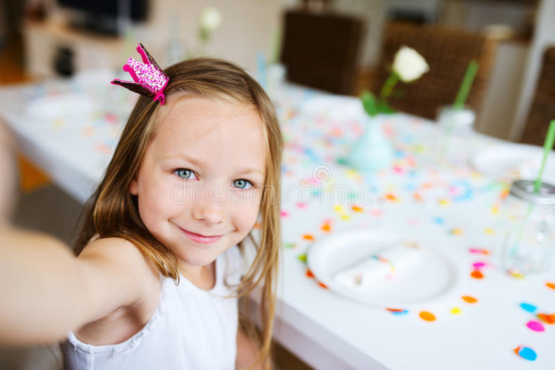 Birthday girl at party. Adorable little girl with princess crown at kids birthday party making selfie royalty free stock photography