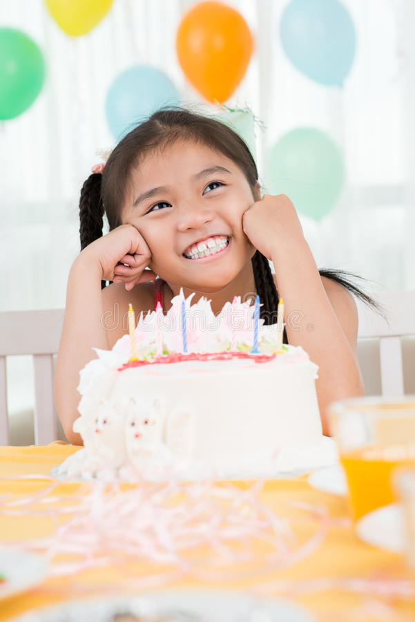 Birthday girl. Vertical image of a cheerful girl sitting in front of the birthday cake royalty free stock photos