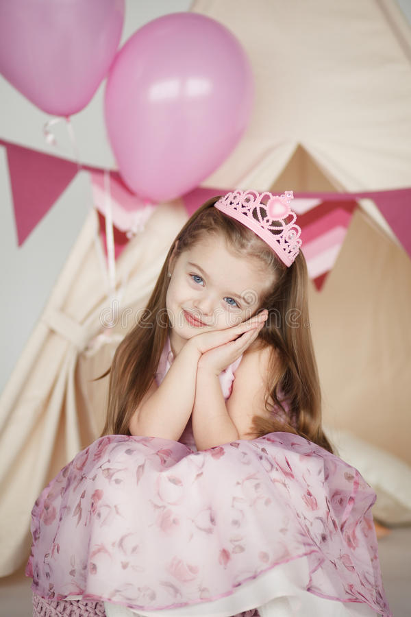 Birthday girl wearing a pink dress and crown stock photography