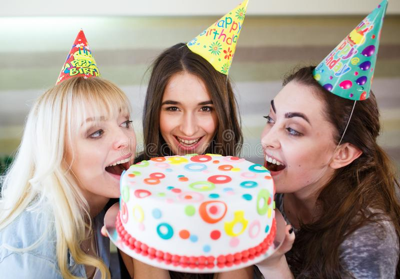 Birthday. Girls bite cake at a birthday party royalty free stock photography