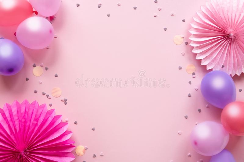 Birthday greeting card. Colorful balloons and paper flowers on pink background. Festive or party background. Flat lay style. stock photos