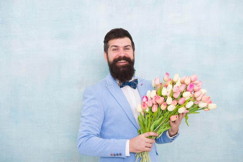 Birthday greetings. Best flowers for girlfriend. Flowers for her. Man bearded suit bow tie hold tulips bouquet stock image