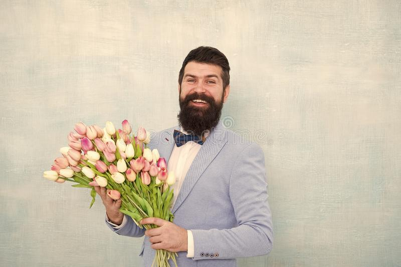 Birthday greetings. Best flowers for girlfriend. Flowers for her. Man bearded suit bow tie hold tulips bouquet. Gentleman making romantic surprise for her royalty free stock photography