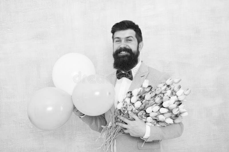 Birthday greetings. Flowers delivery. For someone special. Man bearded gentleman suit bow tie hold air balloons and. Bouquet. Gentleman making romantic surprise royalty free stock photography