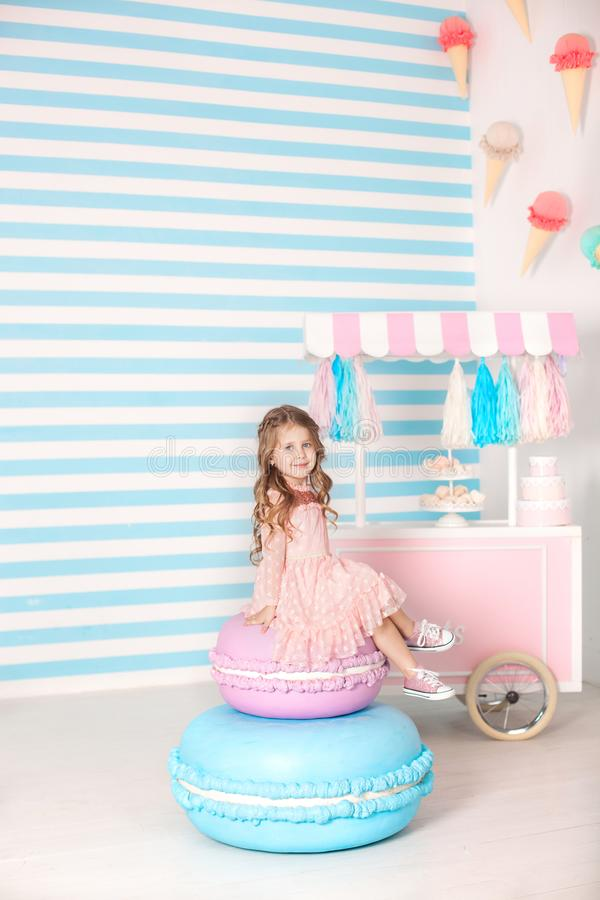 Birthday and happiness concept - happy little girl sitting on a big cake against the background of a candy bar. Decorated room for royalty free stock images