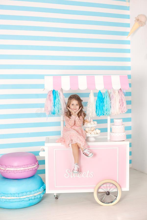 Birthday and happiness concept - happy little girl sitting on a trolley with ice cream and sweets against the background of a cand. Y bar. Large multi-colored royalty free stock images