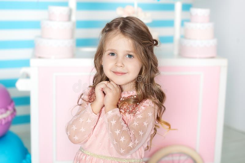 Birthday and happiness concept - happy little girl with sweets on the background of candy bar. Portrait of a beautiful little girl. Little cute girl playing stock photography