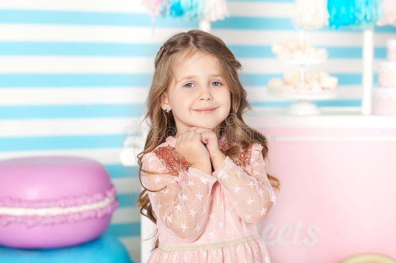 Birthday and happiness concept - happy little girl with sweets on the background of candy bar. Portrait of a beautiful little girl. Little cute girl playing stock photos