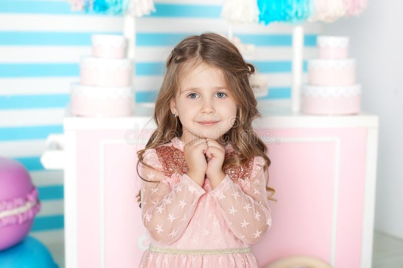 Birthday and happiness concept - happy little girl with sweets on the background of candy bar. Portrait of a beautiful little girl royalty free stock image