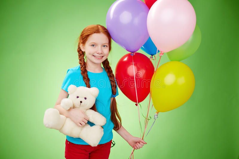 Birthday happiness. Smiling girl with teddybear and balloons looking at camera stock image