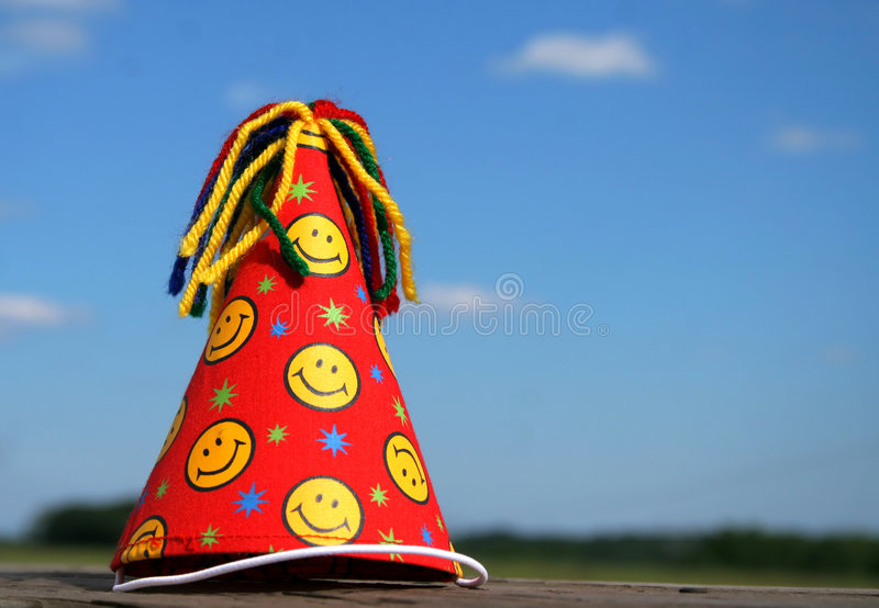 Birthday Hat. A Birthday hat sitting alone outside with a beautiful blue sky and clouds as a background royalty free stock photo