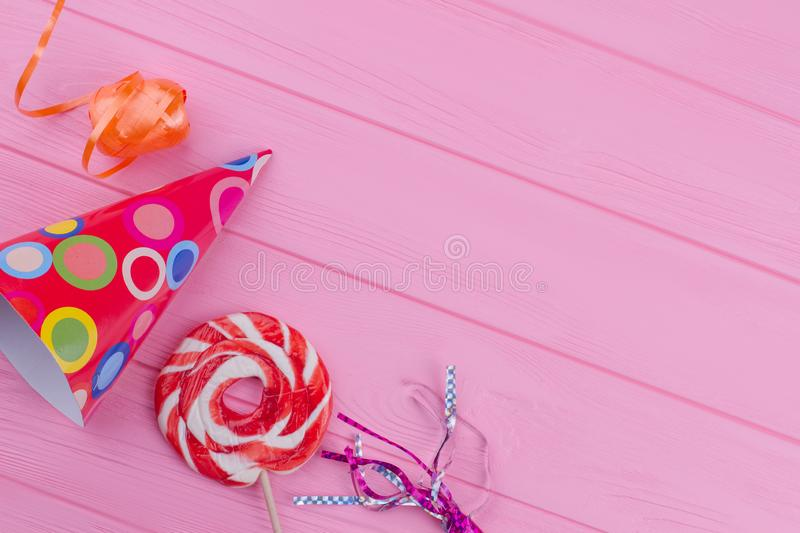 Birthday hat, blower and other party decorations. Birthday party items on pink wooden background with copy space stock photo