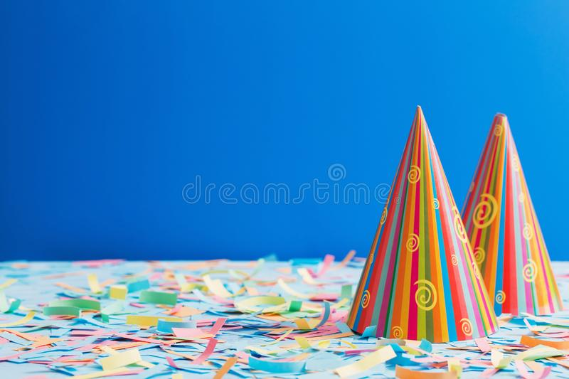 Birthday hat and confetti on blue background. The birthday hat and confetti on blue background stock photo