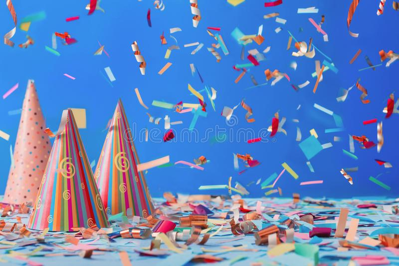 Birthday hat and confetti on blue background. The birthday hat and confetti on blue background stock images