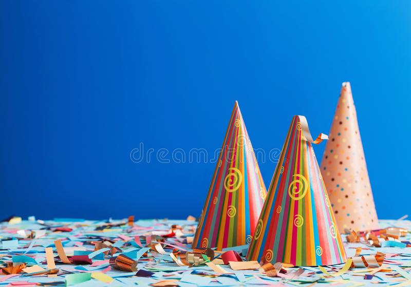 Birthday hat and confetti on blue background. The birthday hat and confetti on blue background royalty free stock photos
