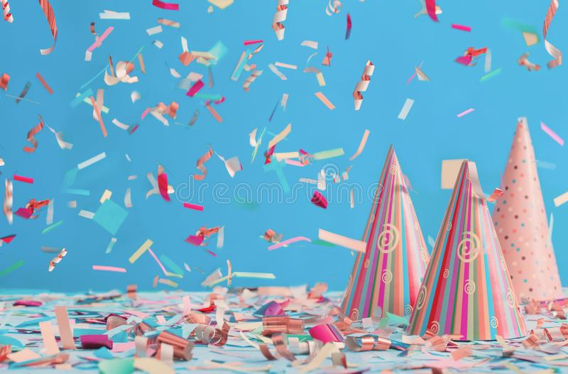 Birthday hat and confetti on blue background. The birthday hat and confetti on blue background royalty free stock photography