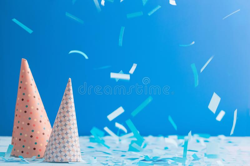 Birthday hat and confetti on blue background. The birthday hat and confetti on blue background royalty free stock image