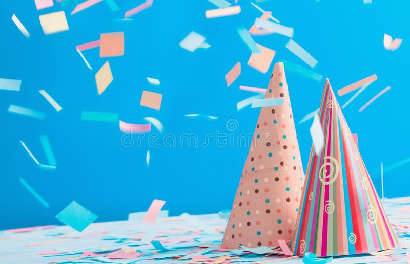Birthday hat and confetti on blue background. The birthday hat and confetti on blue background royalty free stock photo
