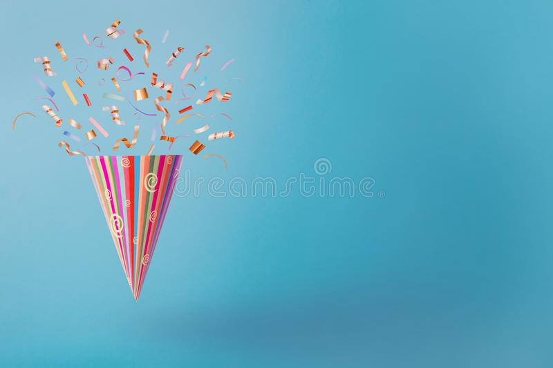 Birthday hat with confetti on blue paper background. The birthday hat with confetti on blue paper background stock image