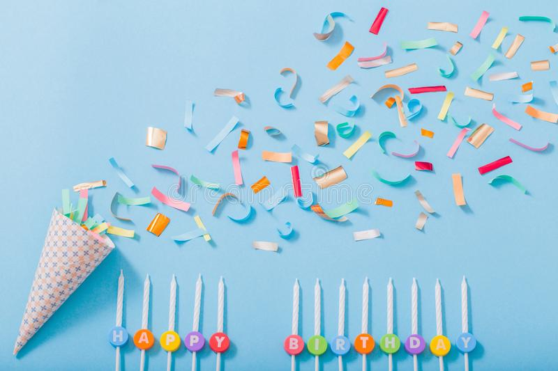Birthday hat with confetti and candles  on paper background. Birthday hat with confetti and candles  on blue paper background royalty free stock images