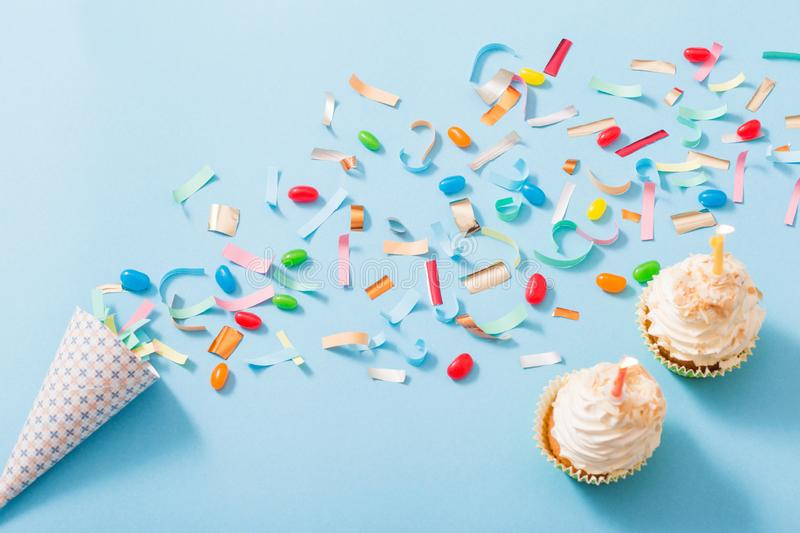 Birthday hat with confetti and cupcake on blue paper background. Birthday hat with confetti and cupcake with burning candle on blue paper background royalty free stock photo