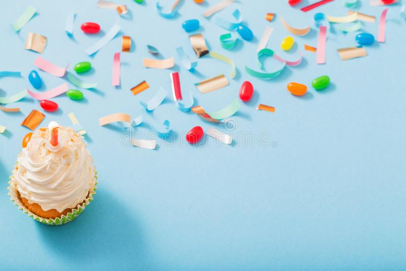 Birthday hat with confetti and cupcake on  paper background. Birthday hat with confetti and cupcake with burning candle on blue paper background stock photos