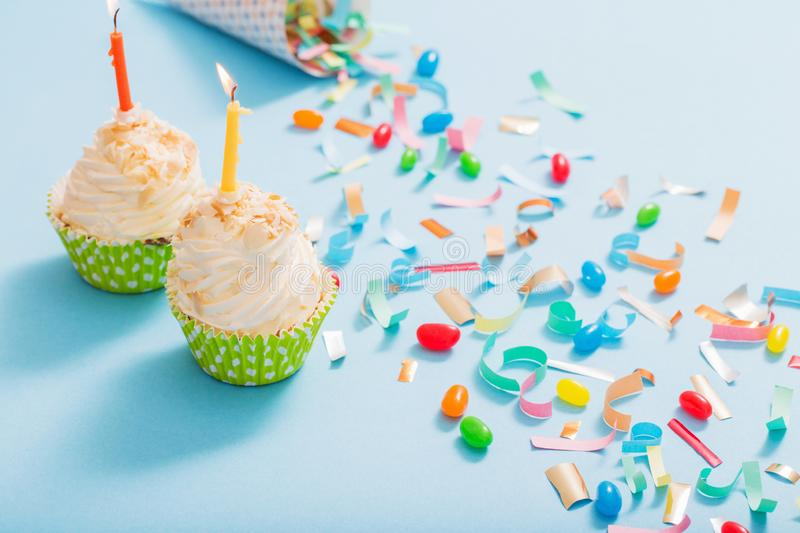 Birthday hat with confetti and cupcake on  paper background. Birthday hat with confetti and cupcake with burning candle on blue paper background stock image