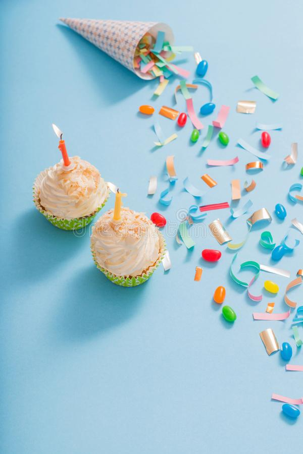 Birthday hat with confetti and cupcake on paper background. Birthday hat with confetti and cupcake with burning candle on blue paper background royalty free stock photography