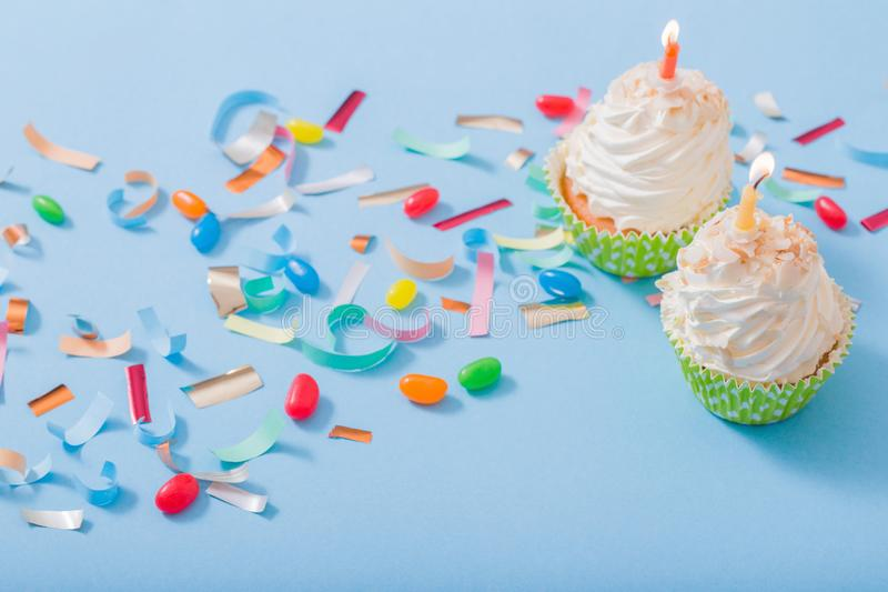 Birthday hat with confetti and cupcake on  paper background stock photography