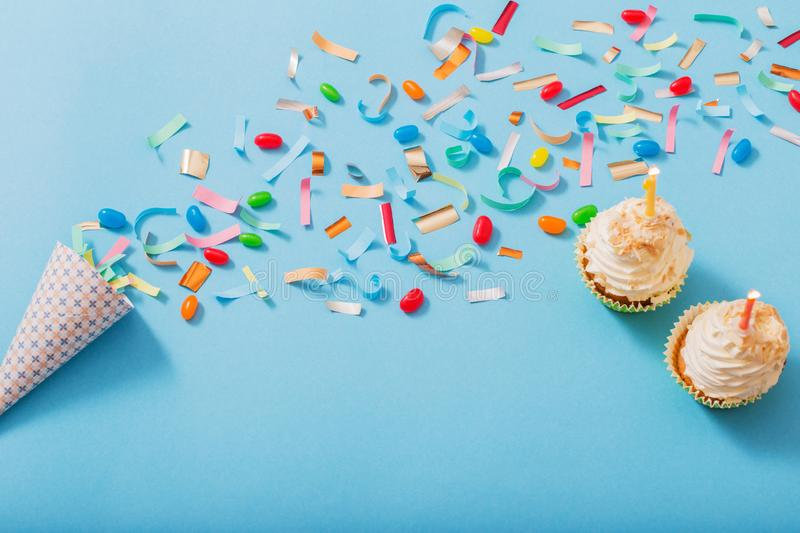 Birthday hat with confetti and cupcake on blue paper background. Birthday hat with confetti and cupcake with burning candle on blue paper background stock images