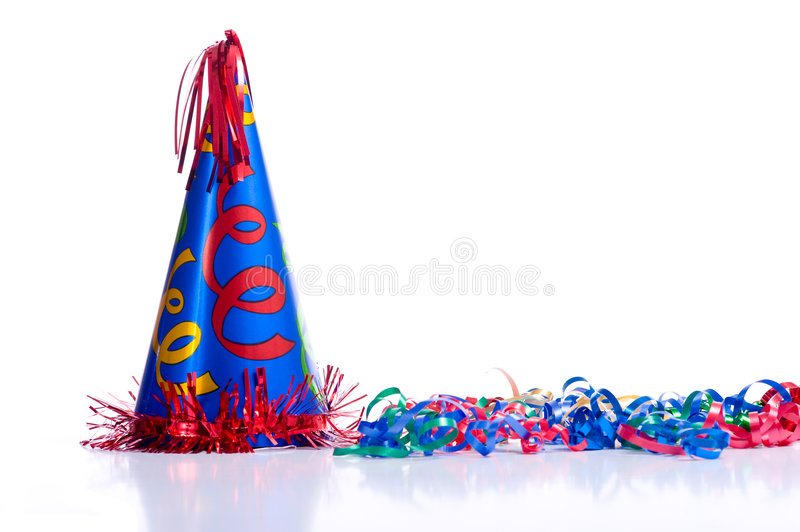 Birthday Hat and Streamers. A brightly colored birthday hat and streamers on a white background with copy space royalty free stock photography