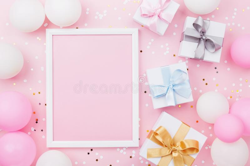 Birthday or holiday mockup with frame, gift box, pastel balloons and confetti on pink table top view. Flat lay composition. Birthday or holiday mockup with royalty free stock photo