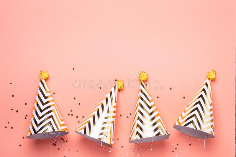 Birthday holiday party concept. Striped golden cones hats and confetti royalty free stock images