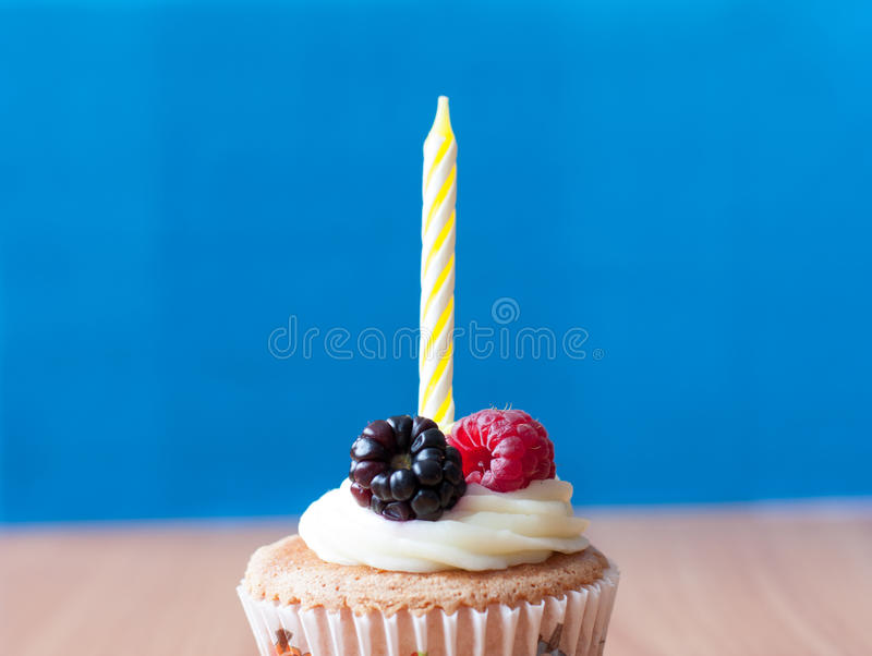 Birthday homemade cupcake. With fresh raspberry and blackberry and cream topping on wooden desk and blue background royalty free stock images