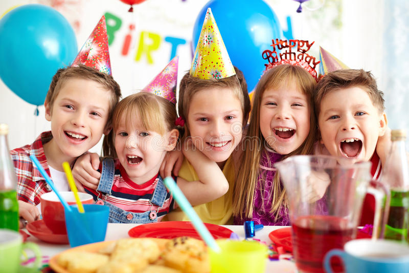 Birthday joy. Group of adorable kids having birthday party stock images