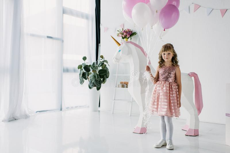 birthday kid holding bunch of air balloons and standing with decorative stock photography