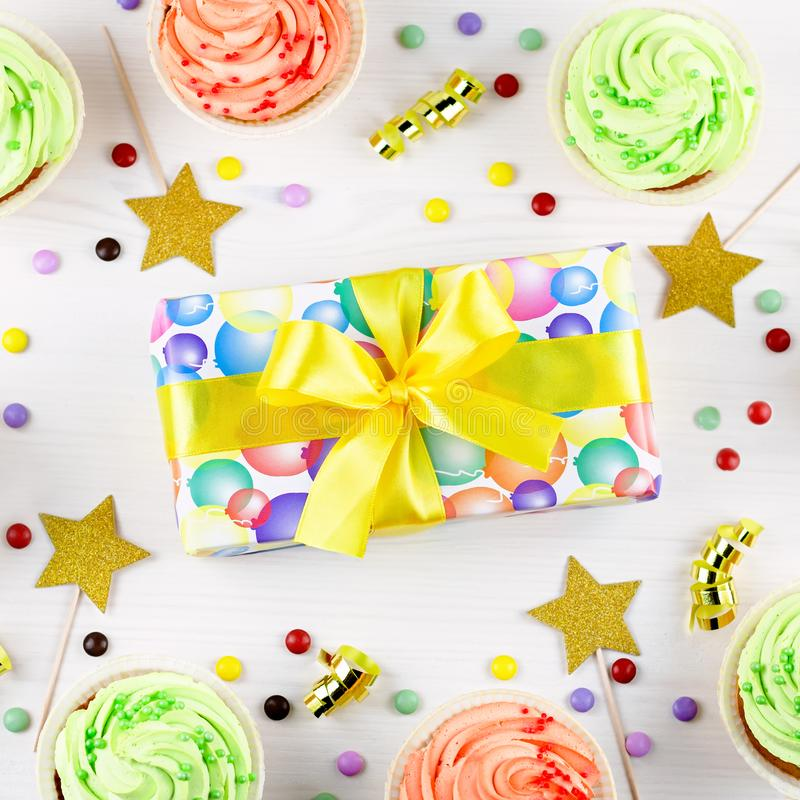 Birthday kids party background with wrapped gifts, confetti, delicious cupcakes, party hats, decorations, top view. Copy space stock photo