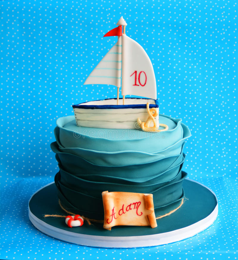 Birthday marine cake for a child. Birthday marine cake decorated with fondant boat, anchor, rope and lifebuoy stock images