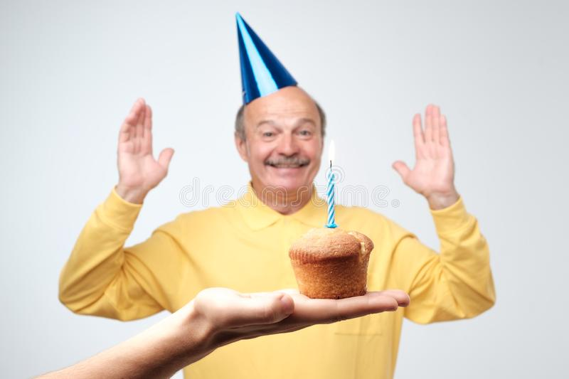 Birthday mature man with party hat is happy on his party stock photography