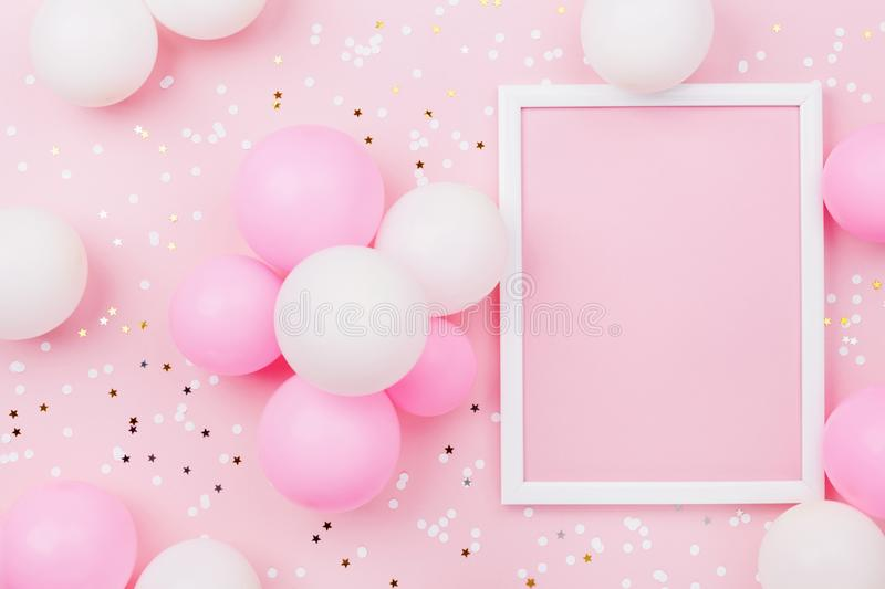 Birthday mockup with frame, pastel balloons and confetti on pink table top view. Flat lay composition. Birthday mockup with frame, pastel balloons and confetti royalty free stock images