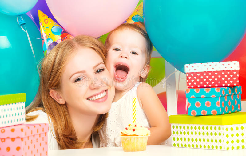 Birthday. mom, daughter, balloons, cake, gifts. Happy birthday. mother and baby daughter with balloons, cake and gifts stock photography