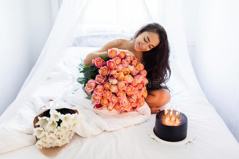 Birthday morning of young woman with huge bouquet of roses and tasty cake. With candles on white bed royalty free stock photo
