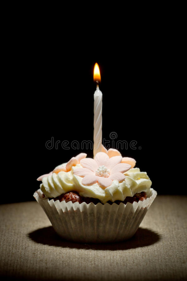 Birthday muffin with small burning candle stock images