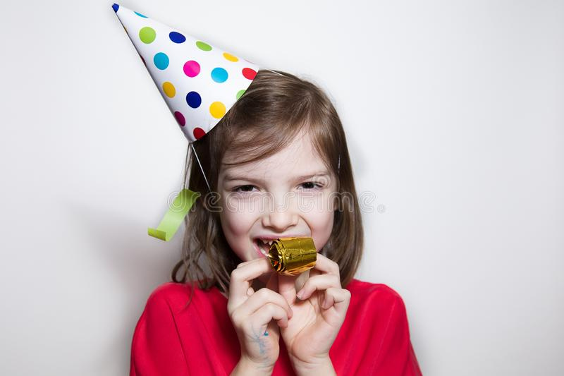 A child on a white background celebrates a bright event, wears a red dress and a cap. stock images