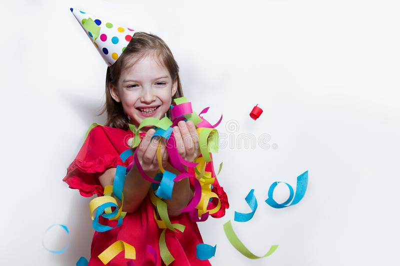 A child on a white background celebrates a bright event, wears a red dress and a cap. stock photos